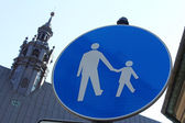 Pedestrian sign with church tower in the background — Stock Photo