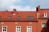 Red building with tile roof against blue sky — Stock Photo