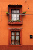 Intensive orange wall with two vintage windows — Stock Photo