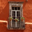 Vintage window with balcony on orange wall — Stock Photo