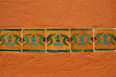 Ornamental tiles in a row on orange wall — Stock Photo
