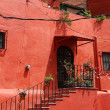 Front side of red mexican building with stairs and windows — Stock Photo