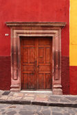 Wooden door in red wall. typical mexican architecture — Stock Photo