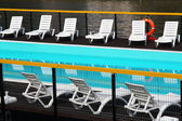 Swimming pool with white chairs — Stock Photo