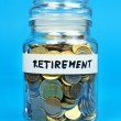 Jar with coins with retirement label on blue background — Stockfoto