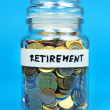 Jar with coins with retirement label on blue background — Stock Photo
