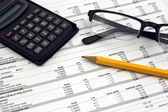 Glasses, calculator and pencil on paper bills — Stock Photo