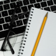 Closeup of glasses, notebook and pencil on silver laptop — Stock Photo