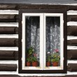 Window with flowers in wall of old wooden house — Stock Photo