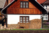 Wooden house with pile of wood logs ready for winter — Stock Photo