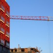 Apartment house and house under constuction with crane — Stock Photo