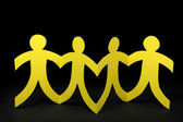 Yellow paper people on black background — Stock Photo