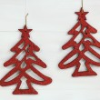 Two shiny red christmas trees on white wooden background — Stock Photo