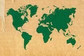 段ボールの背景に緑の世界地図 — ストック写真