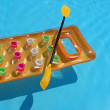 Yellow air mattress with oar in swimming pool — Stock Photo