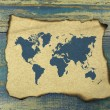 World map on burnt paper on blue old wood background — Stock Photo