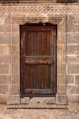Ancient wooden door in stone wall — Stock Photo