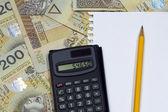 Pencil and calculator on polish money banknotes — Stock Photo
