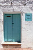 Wooden blue door and whitewashed wall — Stock Photo