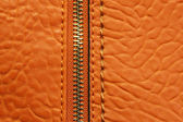 Orange leather background with zipper — Stock Photo