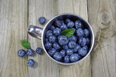 Blueberries in metal cup on wooden background — Stock Photo