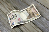 Ten thousand yen banknotes on wooden background — Stock Photo