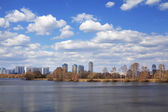 A spring amazing cityscape on the river bank in the distance under the blue sky with beautiful white clouds. — Stock Photo