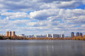 A spring amazing cityscape on the river bank in the distance under the beautiful cloudy sky with blue holes. — Stock Photo