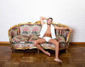Man model couching on sofa — Stock Photo
