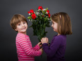 Children romantic with red roses — Stock Photo