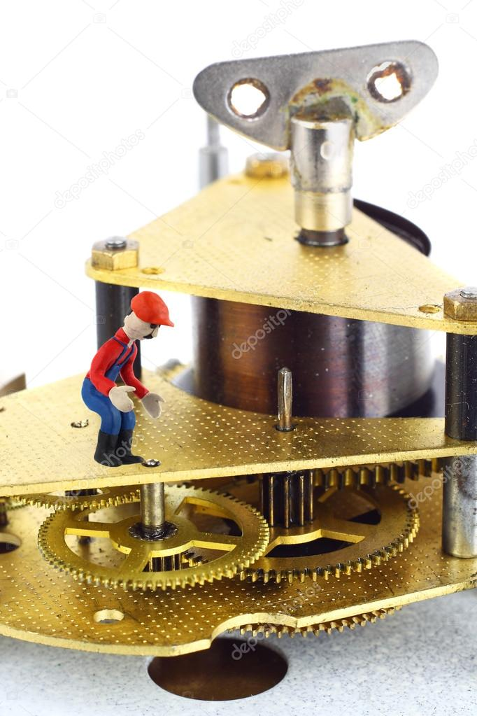 Whatchmaker oversees the work of clockwork. Small plasticine figurine of man in work clothes inside the clock mechanism macro — Stock Photo #14875945