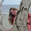 Stock Photo: WomPosing Behind Driftwood on Jekyll Island
