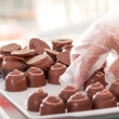 Saleswoman arranging chocolate truffles — Stock Photo