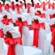 Wedding chairs decorated in white, ribbons and red rose. — Stock Photo #29587843