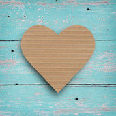 Brown paper in heart shape on vintage wall. — Stock Photo