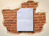 Folded white paper on damaged brick wall background. — Stock Photo