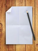Blank crumpled white paper with pencil on vintage wood wall — Stock Photo