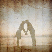 Vintage background of man kissing woman on forehead on the beach — Stock Photo