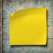 Yellow note paper on vintage grunge wood background — Stock Photo