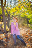 Adorable girl with autumn leaves in park — Stock Photo
