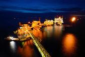 O barco de abastecimento está funcionando a plataforma de petróleo offshore em geral à noite — Fotografia Stock