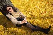 Woman sit on ground be filled with leaves of ginkgo tree in fall — Stock Photo