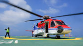 The helicopter landing officer give signal to passenger to embar — Stock Photo