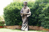 Statue of a boy in a cassock — Stock Photo