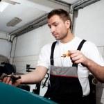 Mechanic checking engine oil — Stock Photo #11986021