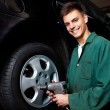 Auto mechanic changing wheel - Stock Photo