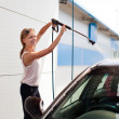 Pretty woman washing the car — Stock Photo