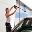 Pretty woman washing the car — Stock Photo