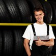 Auto mechanic recommend  tire. Thumbs up - Stock Photo
