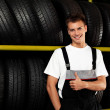 Stock Photo: Auto mechanic recommend tire. Thumbs up